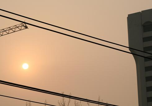 Beijing, China - Sun and smog in a hazy orange-brown sky.