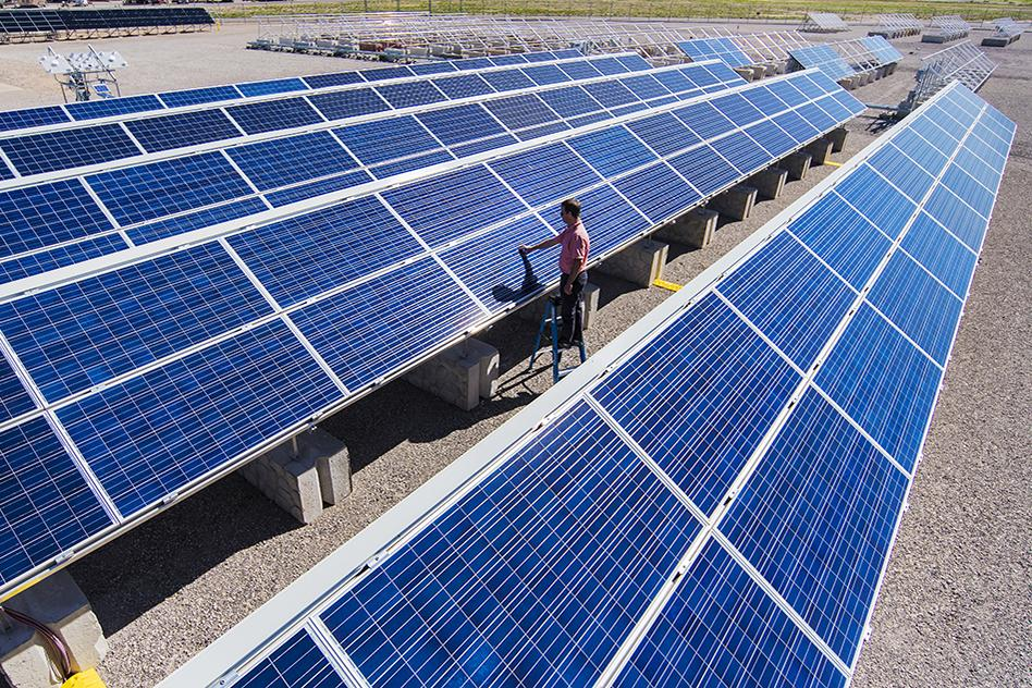 Solar engineer Joshua Stein works on one of several photovoltaic systems being evaluated for industry partners at Sandia National Laboratories in the U.S. Regional Test Centers program. Sandia won a three-year renewal of a Department of Energy contract to manage the RTCs, a network of five sites across the country where industry can assess the performance, reliability and economic viability of solar photovoltaic (PV) technologies. (Photo by Randy Montoya)